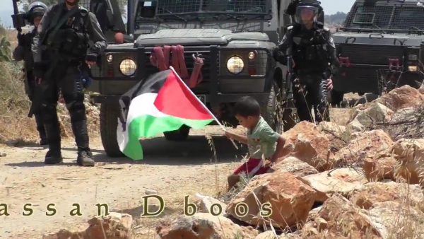 Palestinian child pushed towards soldier video screen shot sitting on rock